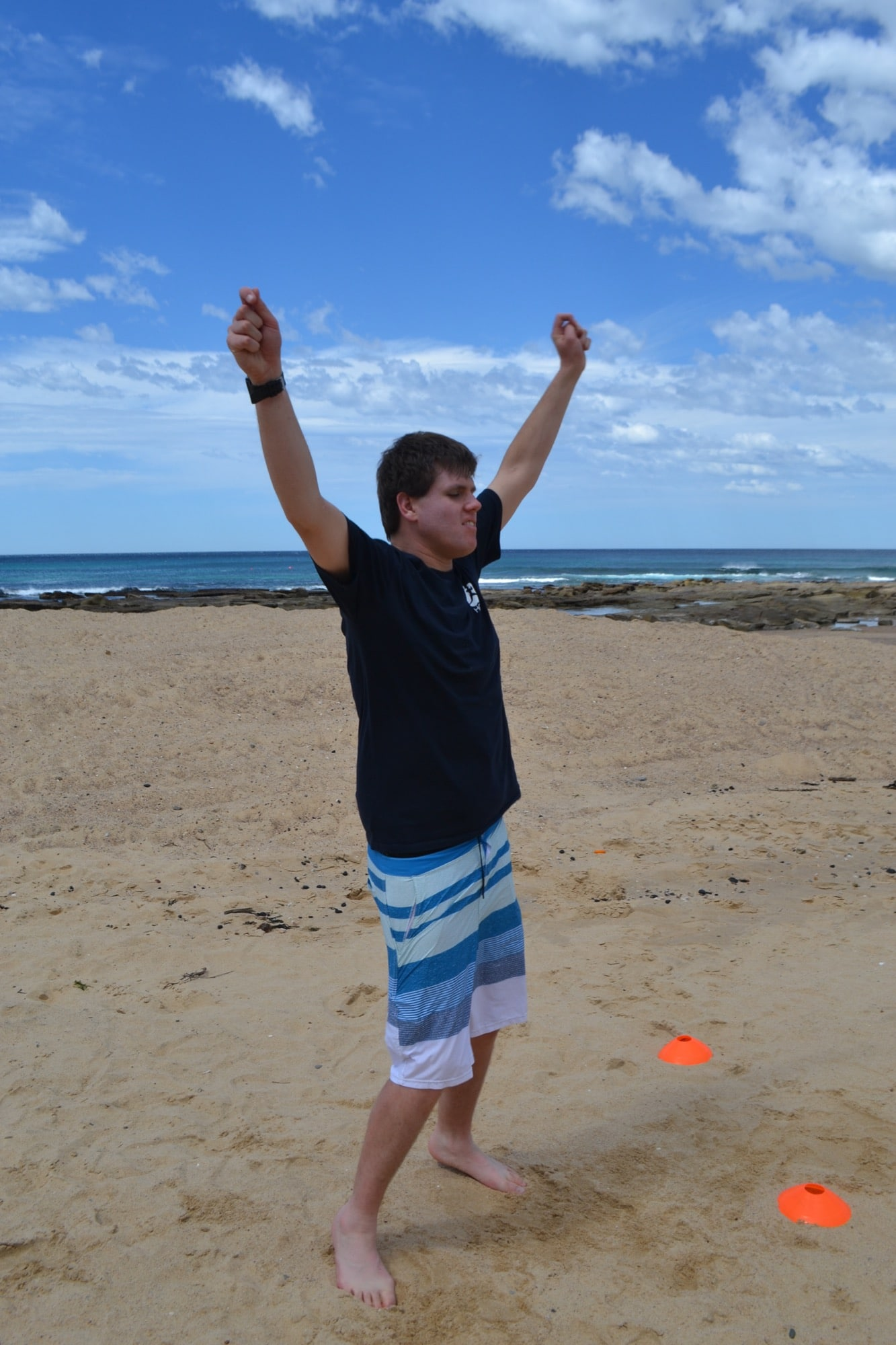 man raising hands celebrating on the beach