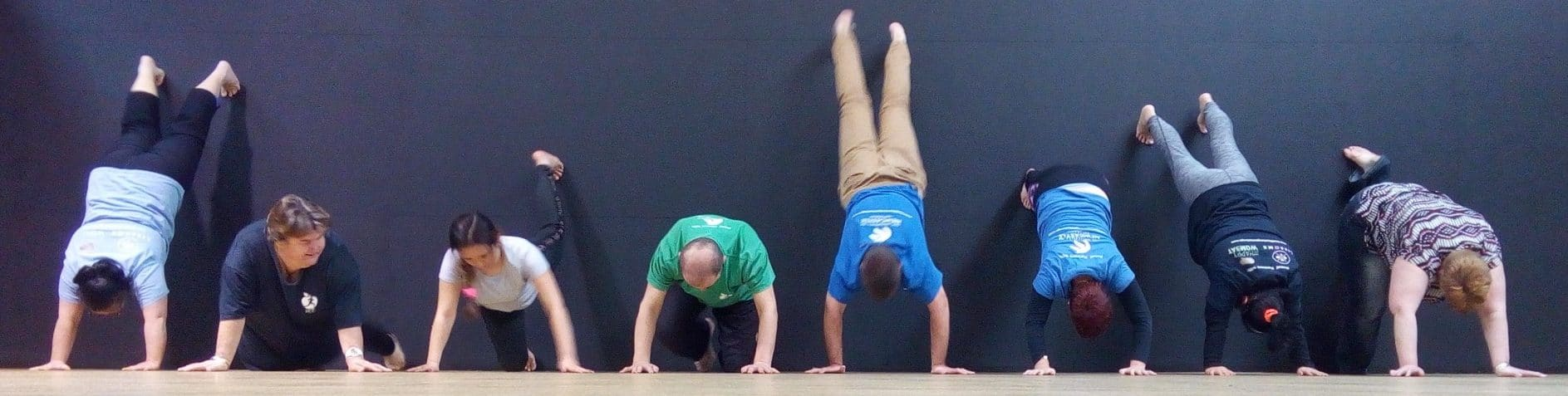 people doing a handstand against a wall